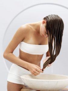 kobieta smaruje włosy odżywką regenerującą