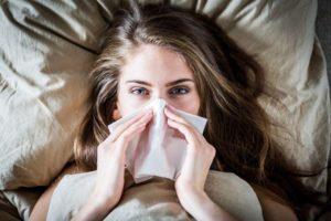 chora kobieta w łóżku dmucha nos bo ma sprawdzony sposób na zatoki