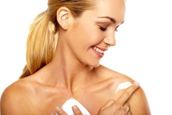 szczęśliwa młoda kobieta smaruje ciało kremem po użyciu mydła